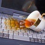 Опрокинутая чашка на клавиатуре с пролитой жидкостью