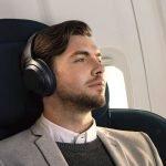 Молодой человек в наушниках сидит в кресле самолёта